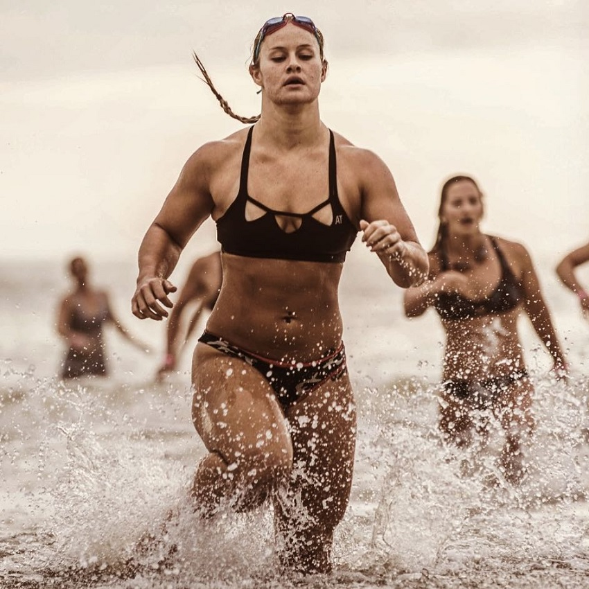 Dani Elle Speegle running in shallow water competing against other athletes