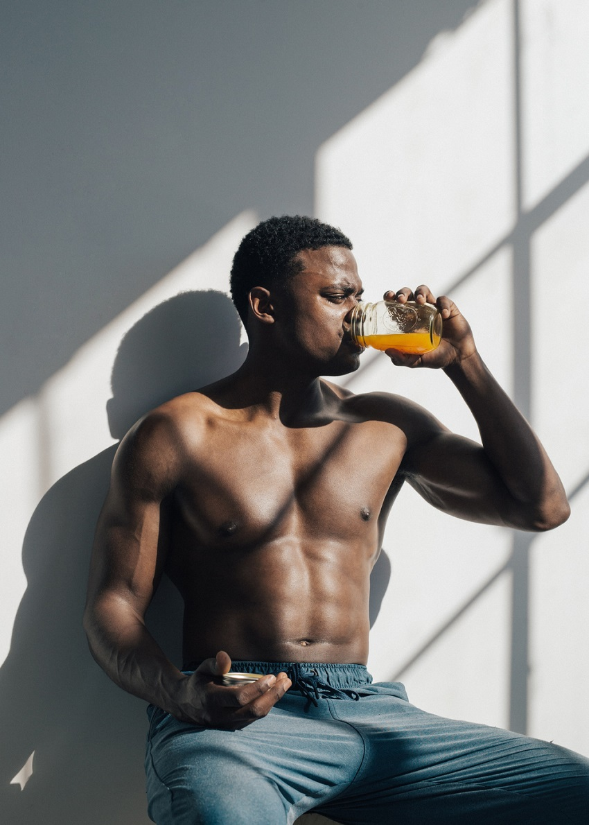 Joe Holder drinking a healthy juice while being shirtless