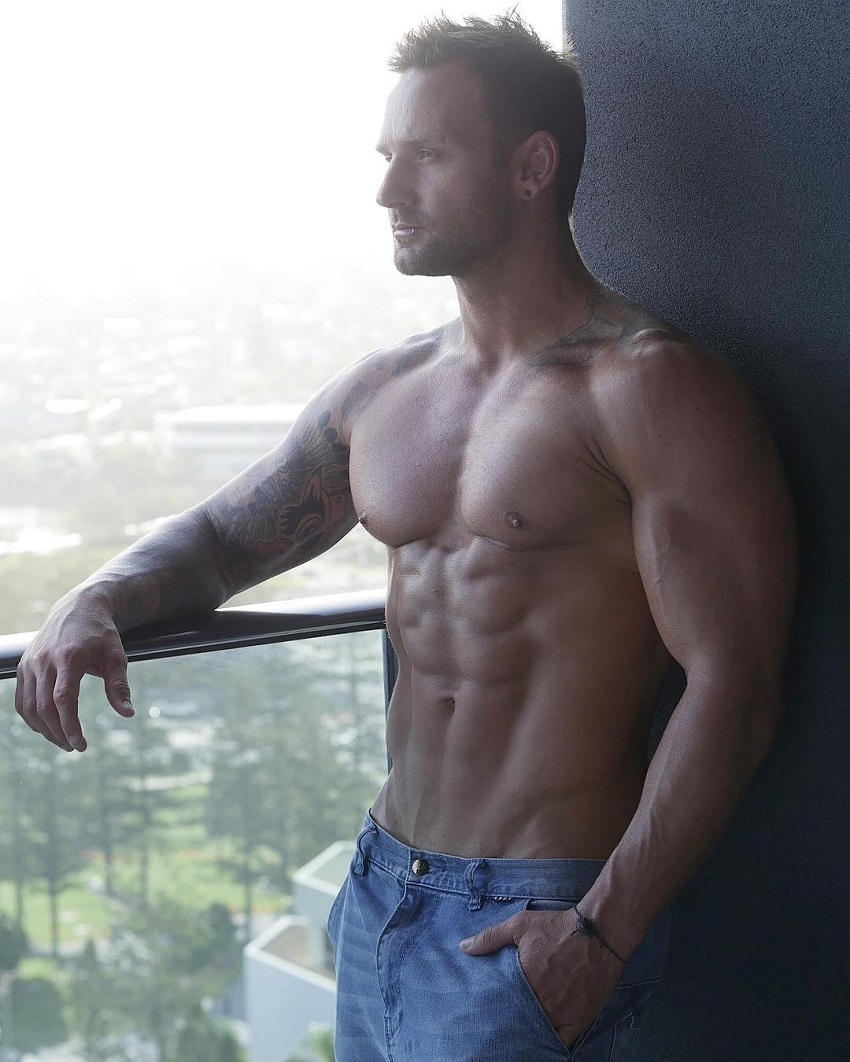 Joel Bushby posing shirtless on the balcony looking muscular and ripped