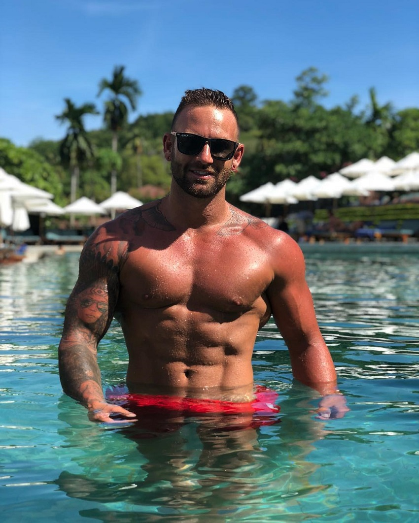 Joel Bushby standing half-way in the pool looking muscular and ripped