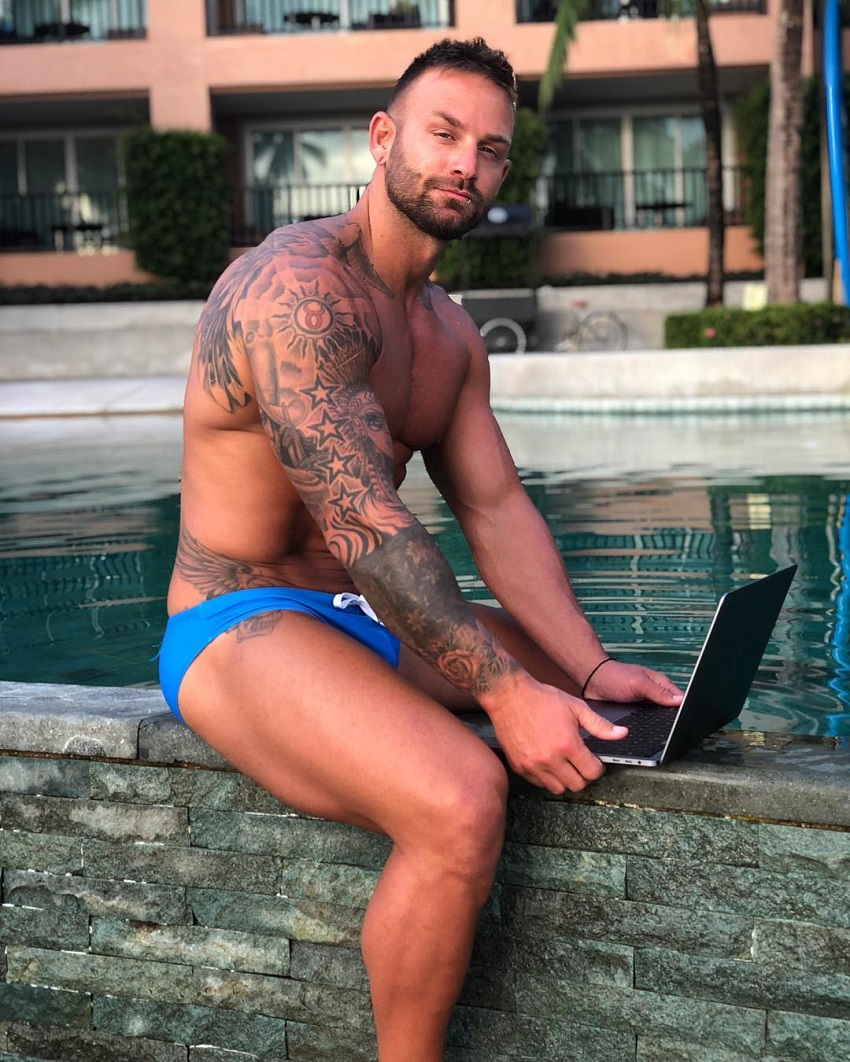 Joel Bushby sitting near a pool with his laptop, looking fit and muscular