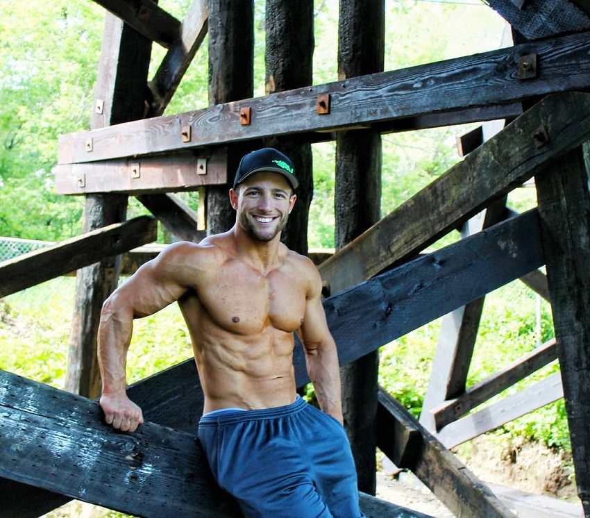 Jonathan Plante leaning against a construction, posing shirtless outdoors