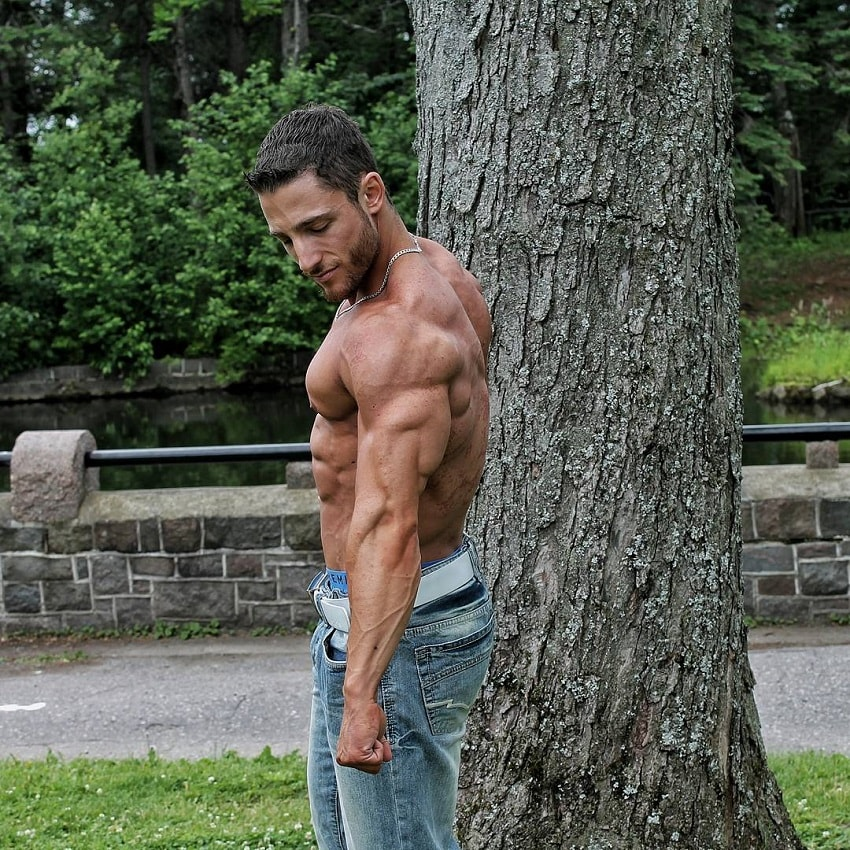 Jonathan Plante standing shirtless by a tree flexing his triceps