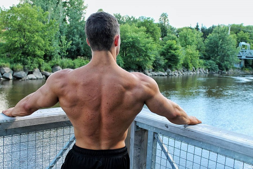 Jonathan Plante standing shirtless by a fence overlooking a river