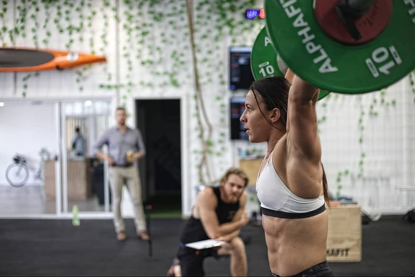 Kara Webb Saunders doing an overhead press with a barbell, looking fit and strong