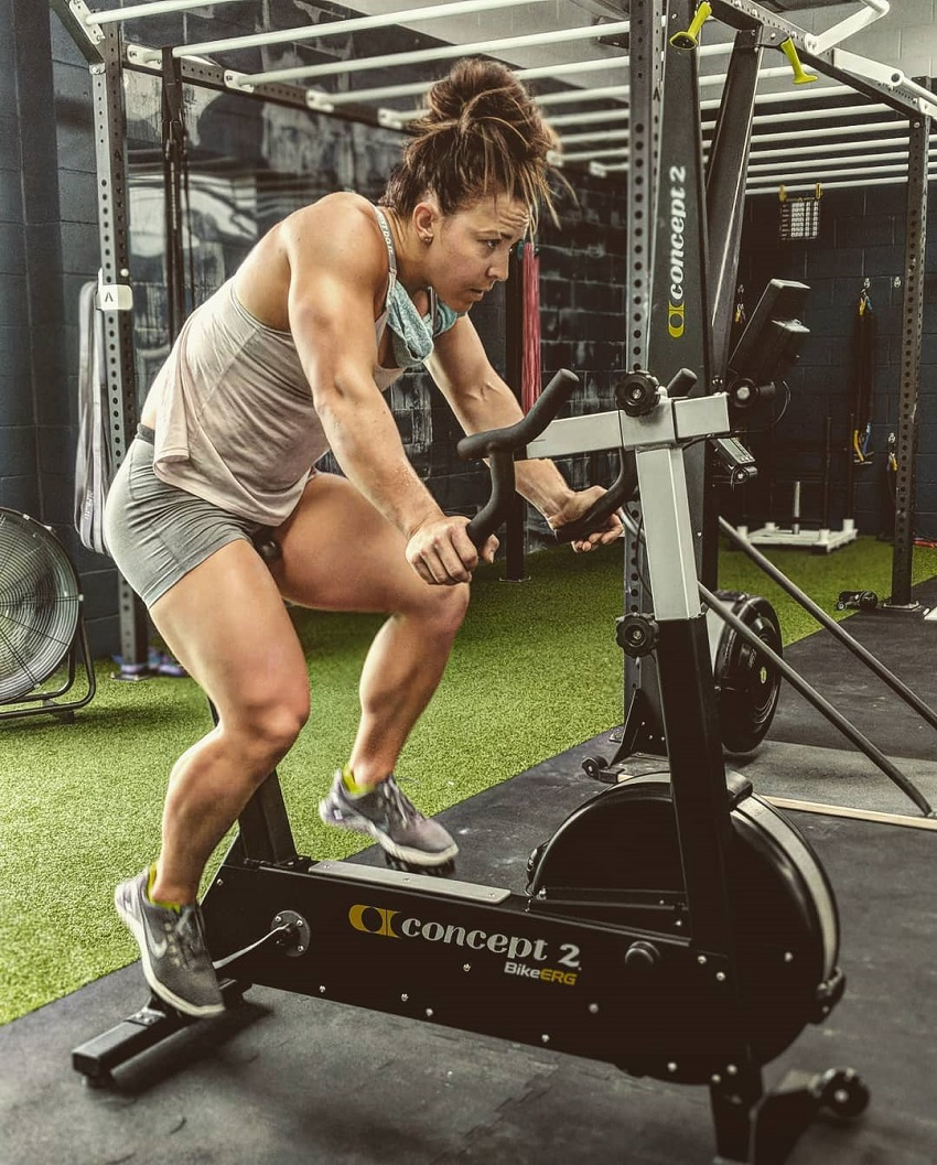 Kara Webb Saunders doing cardio on a stationary bicycle