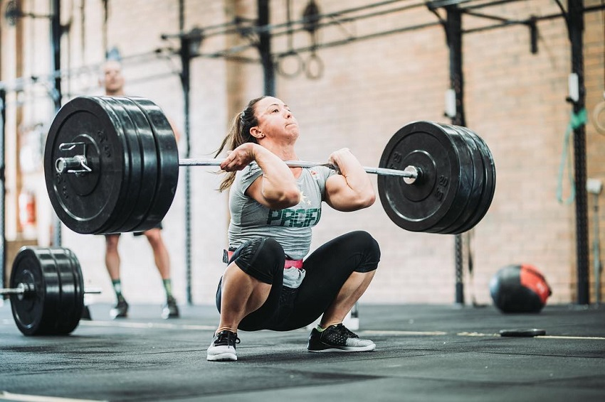 Kara Webb Saunders lifting a barbell loaded with weights during CrossFit training