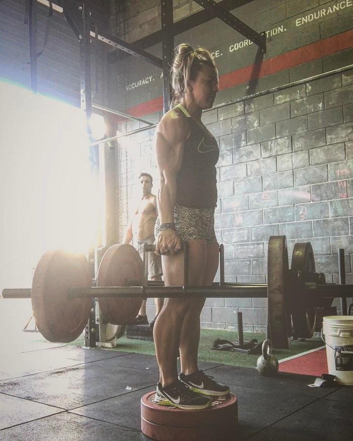 Kara Webb Saunders lifting heavy bars during a CrossFit training