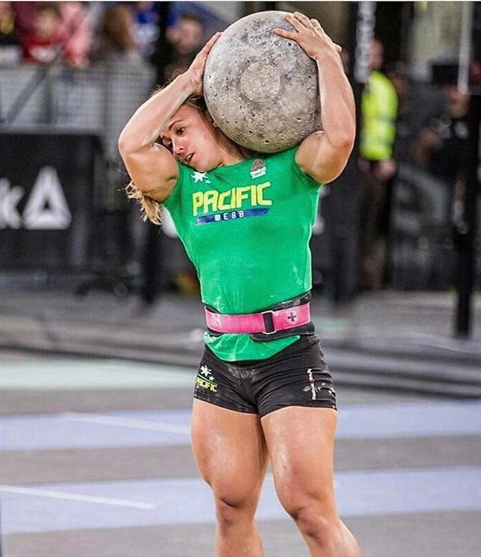 Kara Webb Saunders lifting a heavy rock boulder her legs looking big and aesthetic
