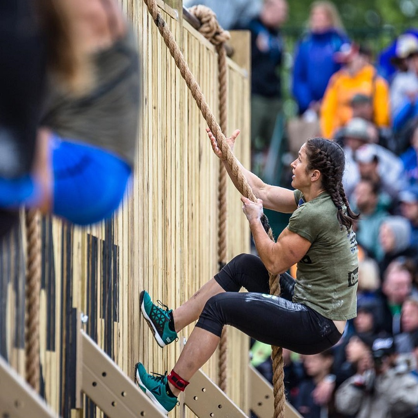 Kari Pearce climbing a rope during a CrossFit event