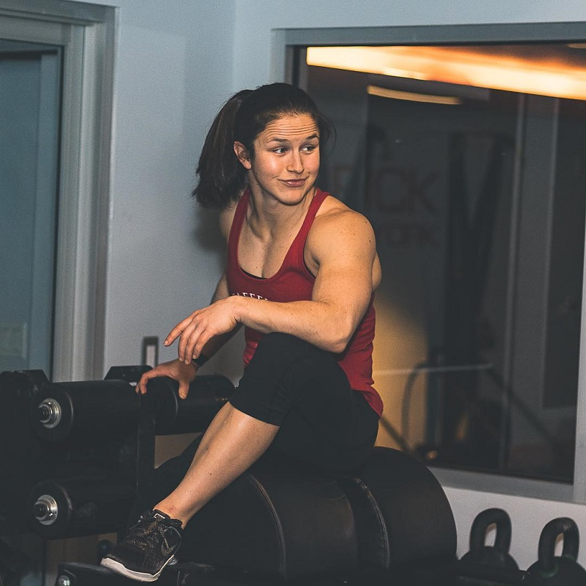 Kari Pearce sitting on a dumbbell rack looking fit and strong