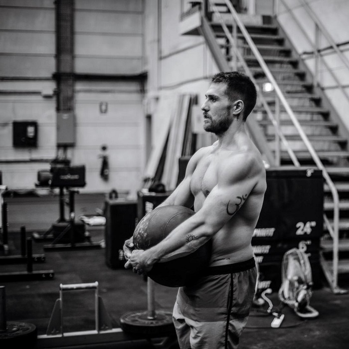 Khan Porter posing shirtless while lifting a heavy medicine ball