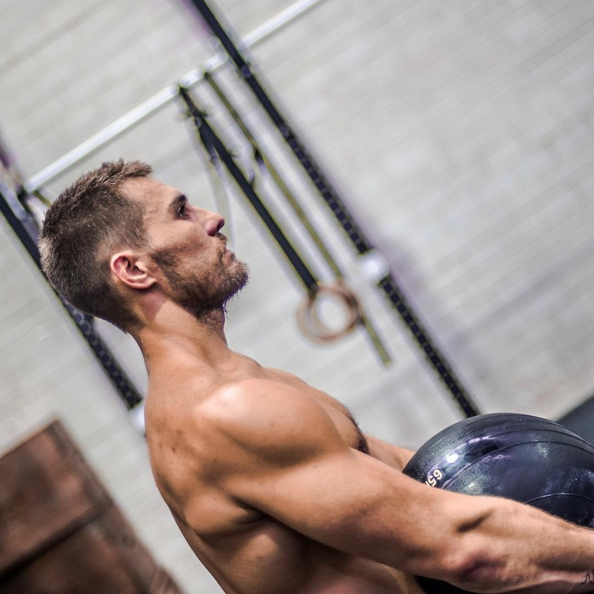 Khan Porter lifting a heavy medicine ball while being shirtless