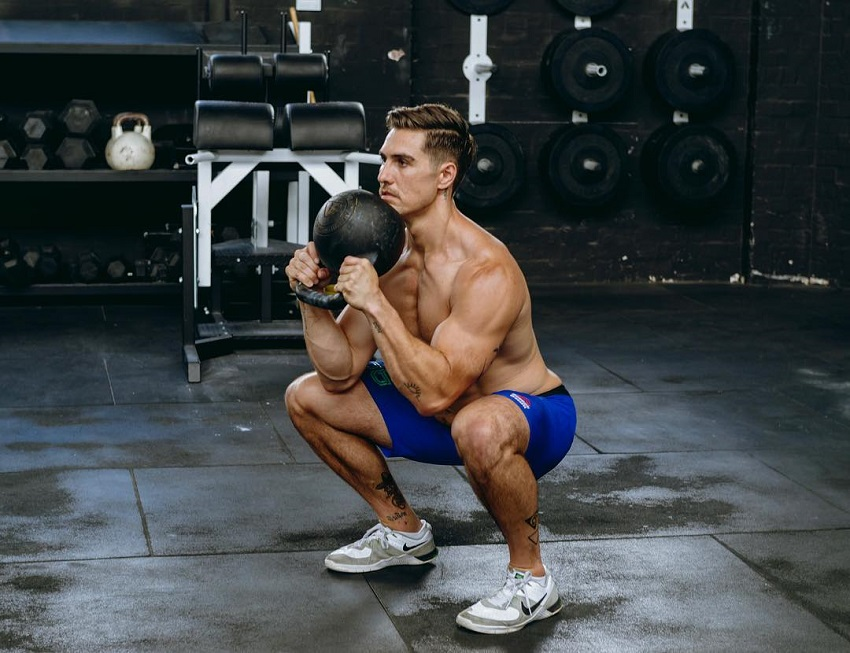Khan Porter doing a squat with a kettlebell in his hands