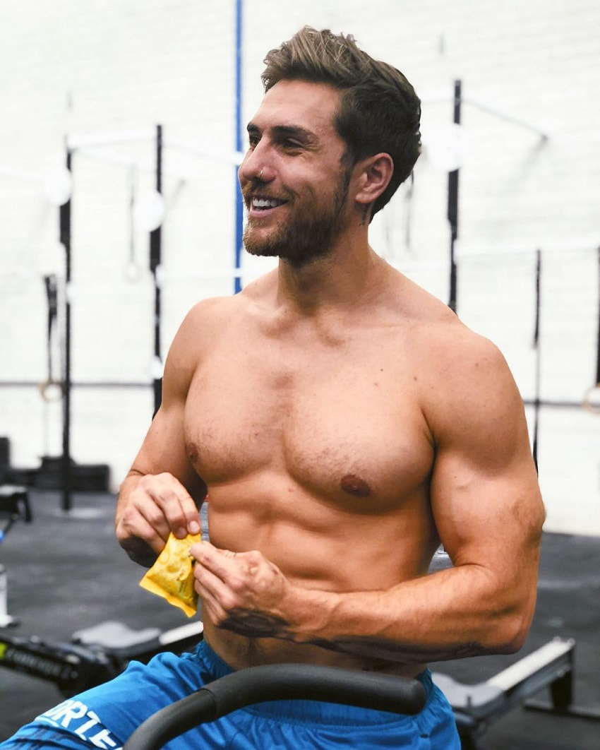 Khan Porter eating a snack while being shirtless in a CrossFit gym, looking ripped and strong