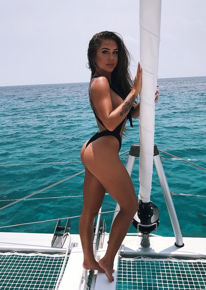 Laura Amy standing on a boat posing for a photo in her bikini