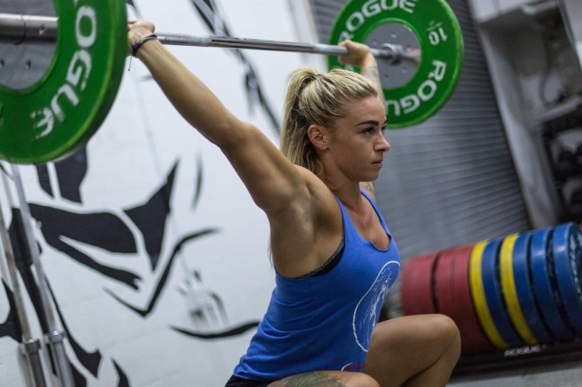 Lauren Herrera lifting a heavy barbell overhead