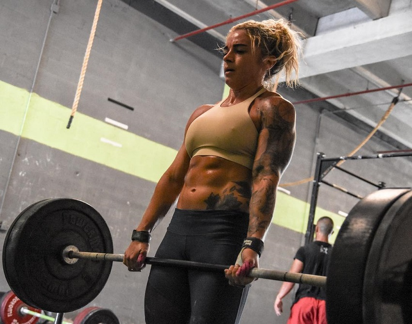 Lauren Herrera lifting a heavy barbell loaded with weights, her abs popping out