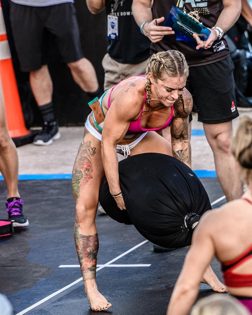 Lauren Herrera lifting a heavy sand bag during a CrossFit event