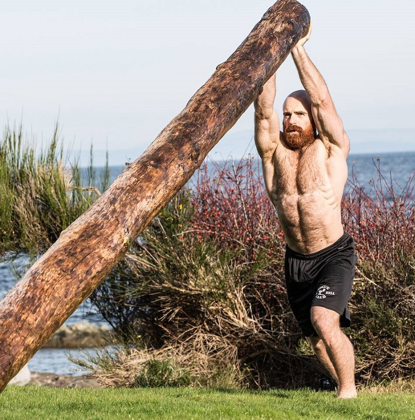Lucas Parker lifting a heavy log while being shirtless