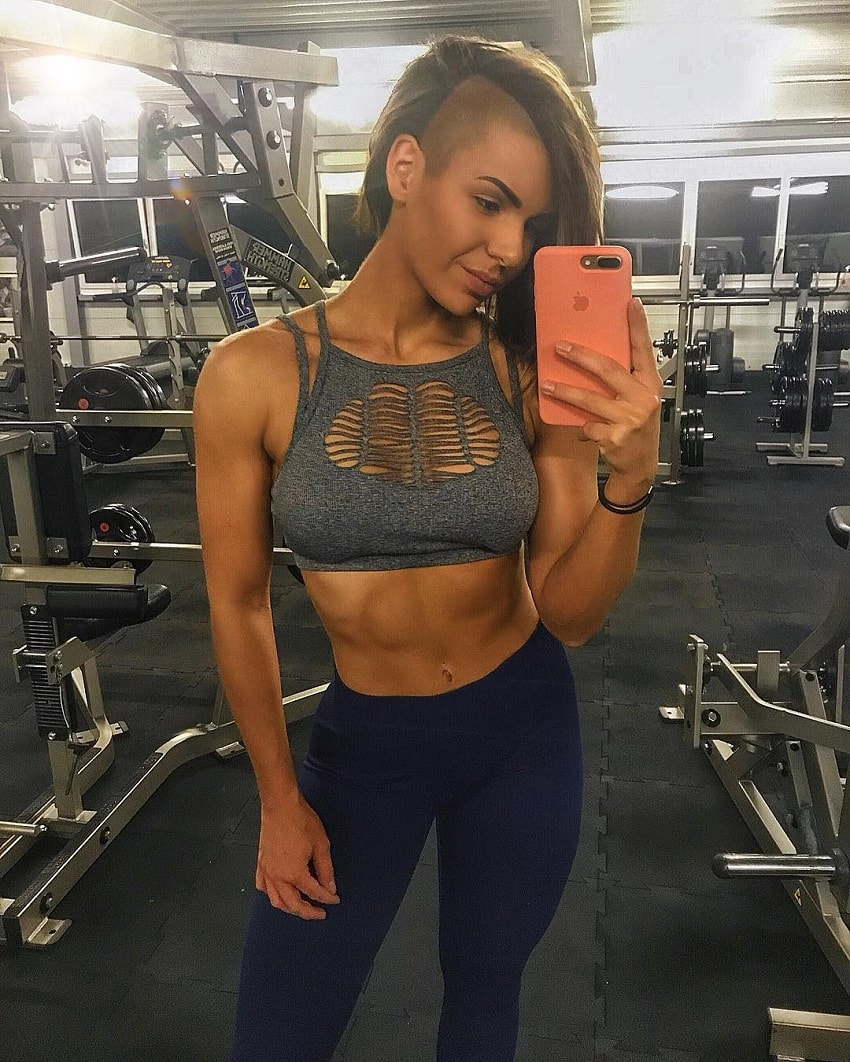 Michell Kaylee taking a selfie of her toned midsection in a gym