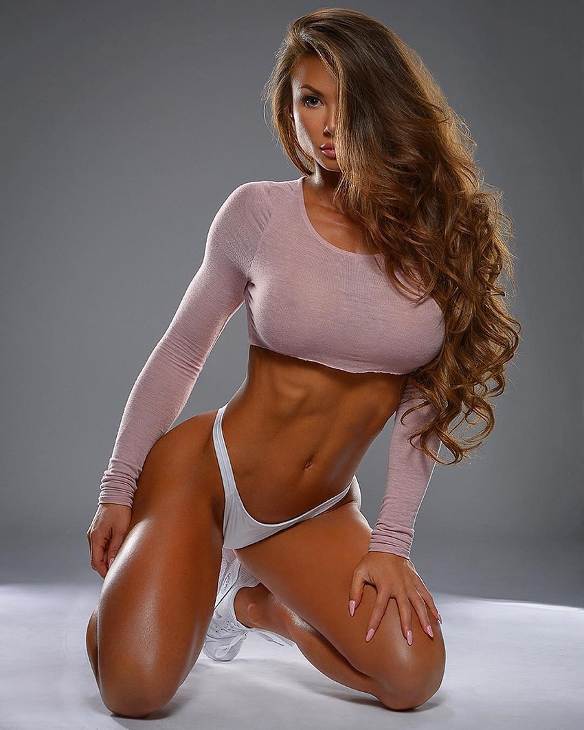 Michie Peachie kneeling in a photo shoot showing off her ripped midsection