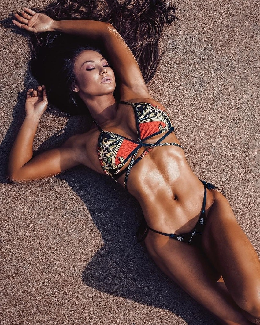 Michie Peachie lying on the beach looking fit and toned