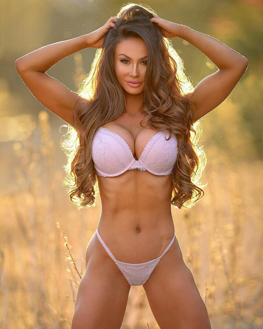 Michie Peachie posing outdoors in a grass field showing her fit physique