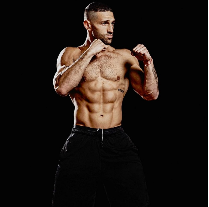 Noah Neiman posing shirtless in a boxing stance looking fit and lean