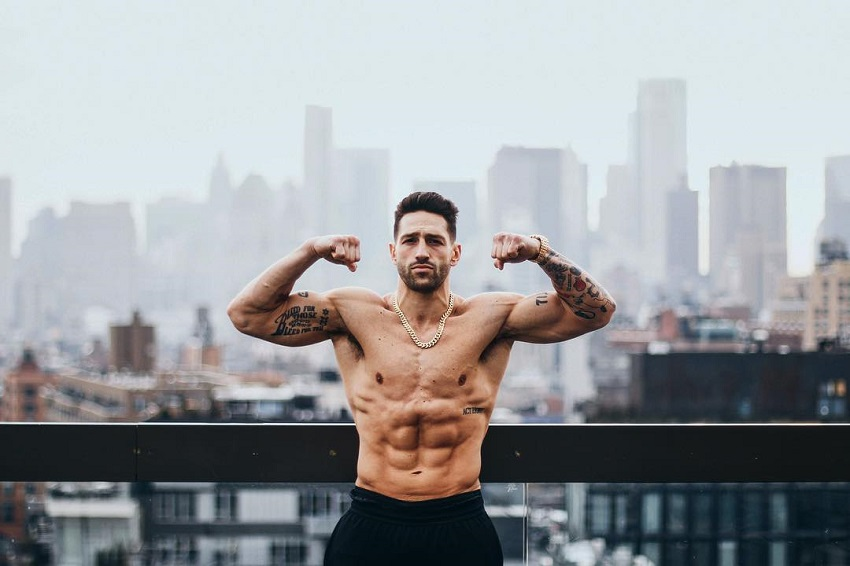 Noah Neiman doing a shirtless front double biceps flex for a photo with a huge city in the background