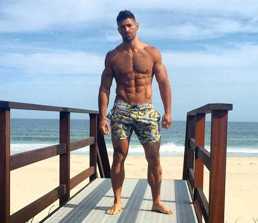 Noah Neiman posing shirtless by the beach looking strong and aesthetic