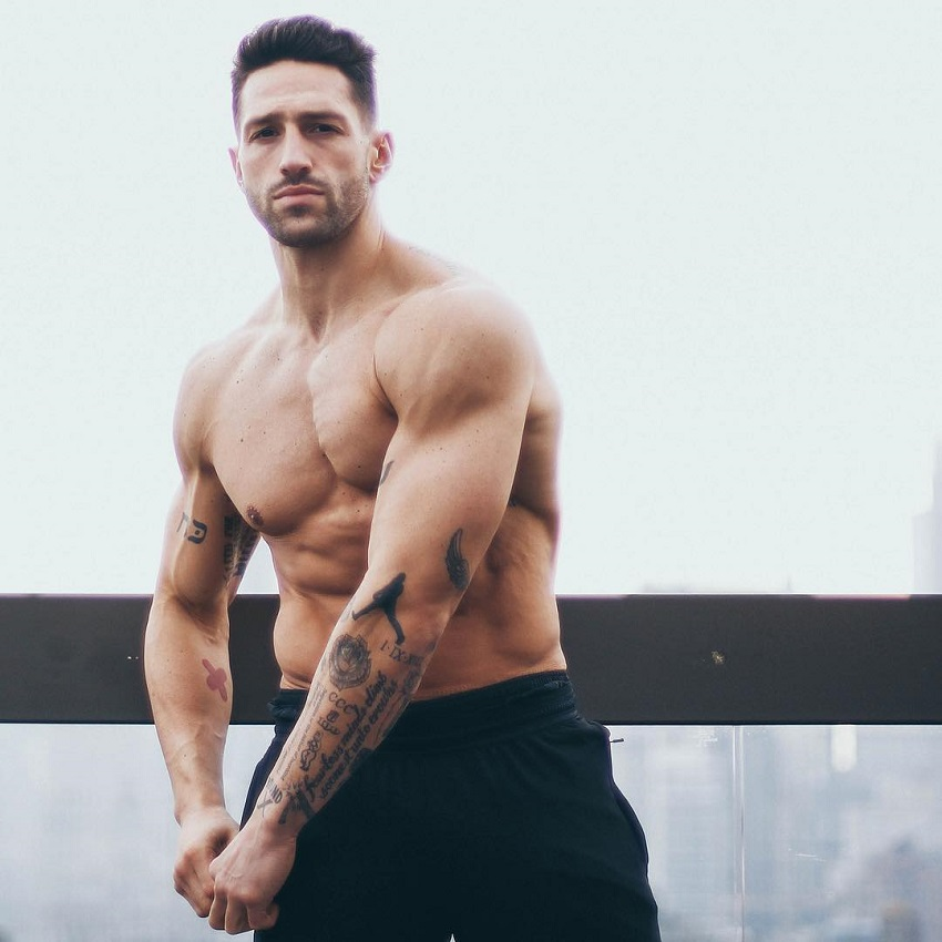 Noah Neiman posing shirtless for a photo looking muscular and strong