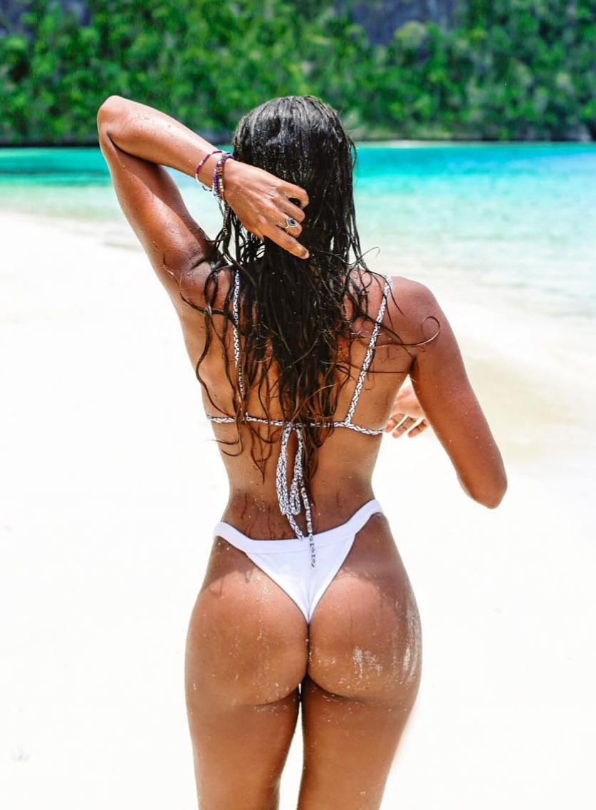 Rosanna Cordoba standing on the beach in her white bikini, showing off her curvy and toned glutes