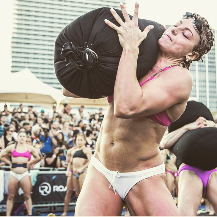Tiffany Szemplinski carrying a heavy bag of sand during a CrossFit contest