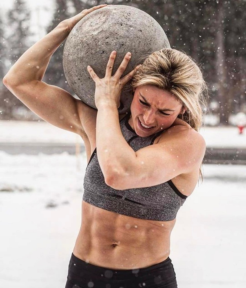 Tiffany Szemplinski carrying a heavy boulder on her shoulders