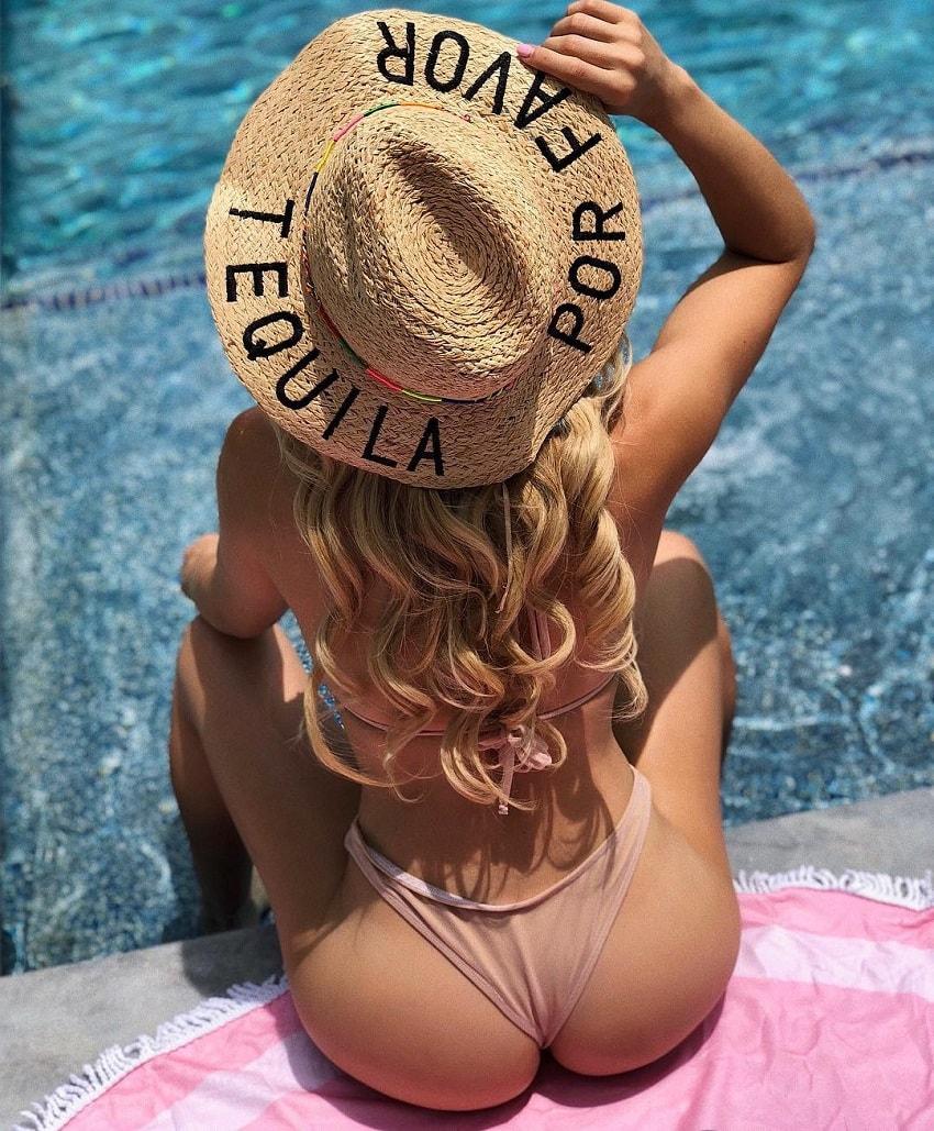 Valeria Orsini sitting by the pool in her bikini