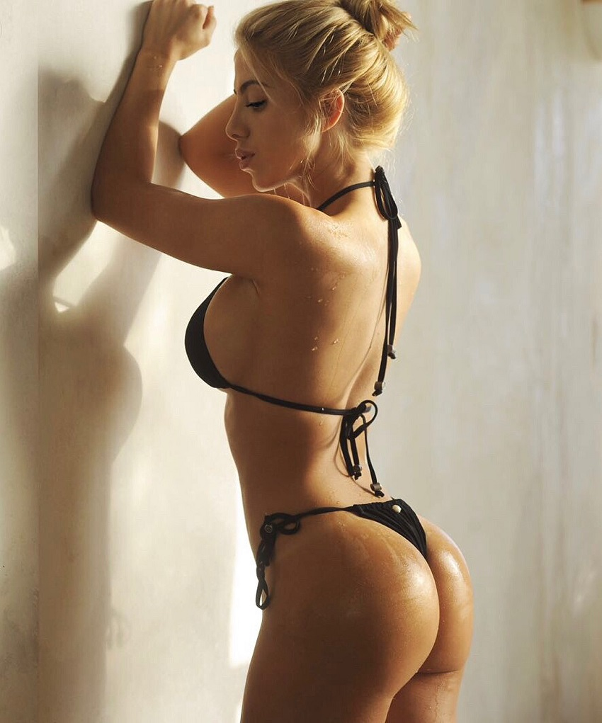 Valeria Orsini leaning against the wall showing off her curvy glutes