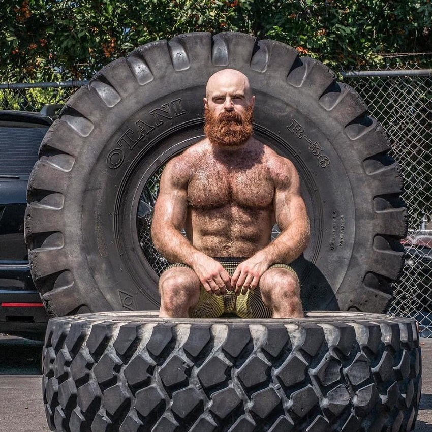 Lucas Parker sitting shirtless on a big tire, looking muscular