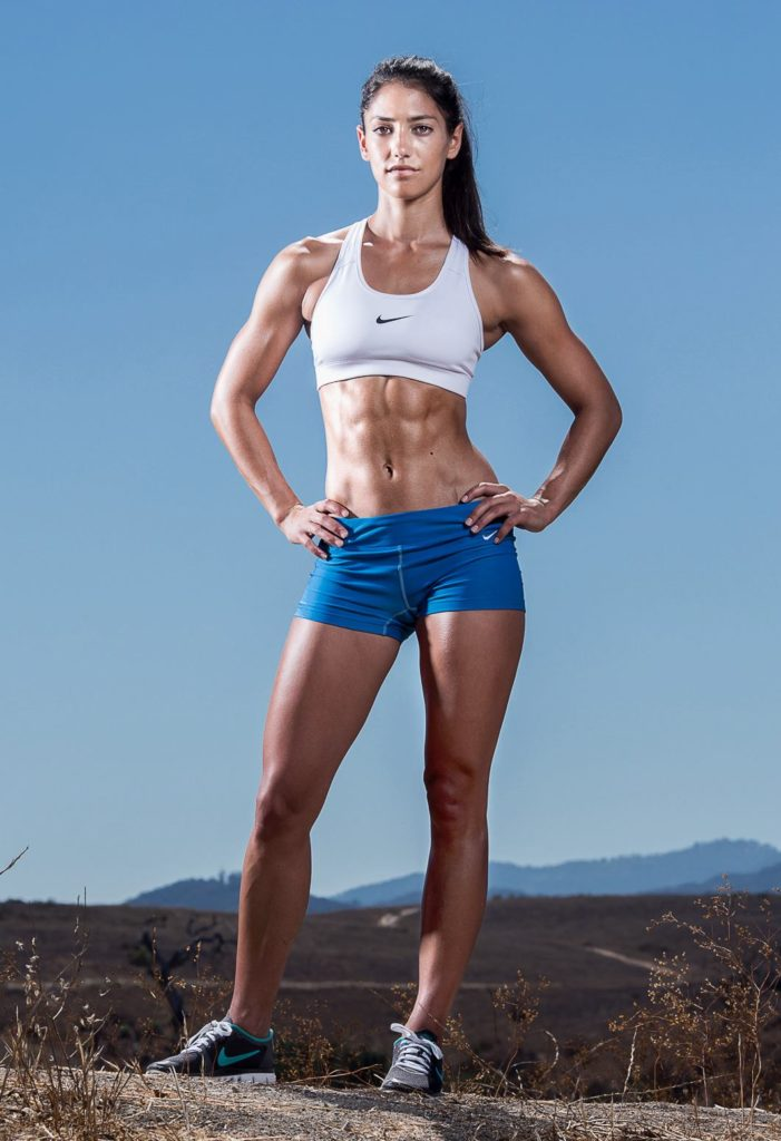 Allison Stokke posing outdoors in her sports wear looking fit and lean