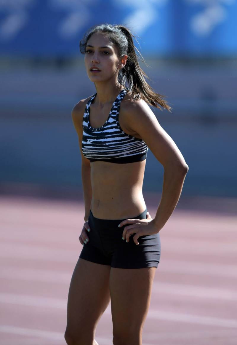 Allison Stokke standing on a track field looking fit and lean