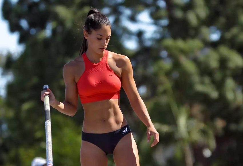 Allison Stokke practicing pole vault outdoors with her abs looking toned