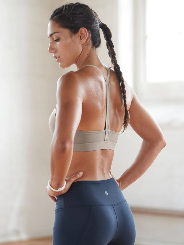Allison Stokke posing for a picture showing off her lean back and glutes in black leggings