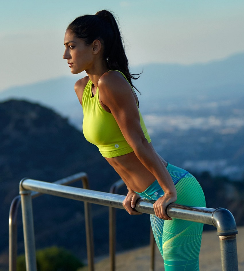 Allison Stokke leaning against a metal bar looking fit and toned