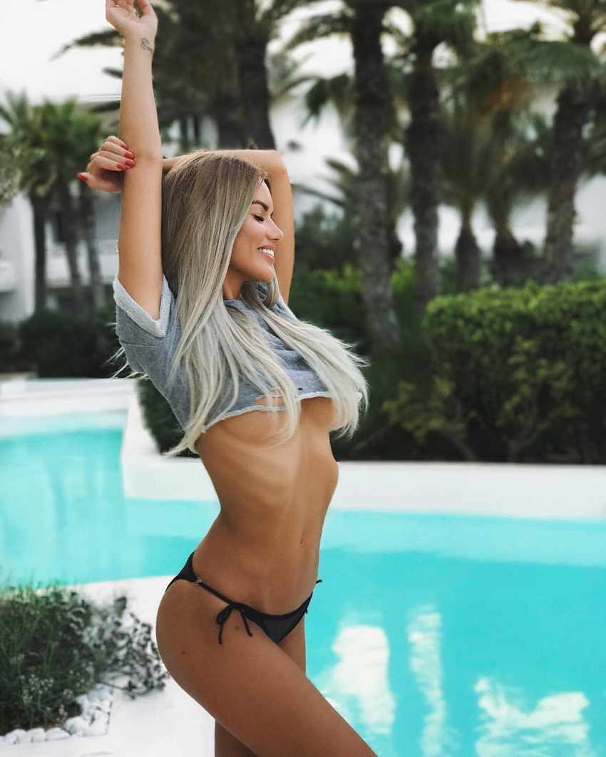 Anella Miller posing by the pool looking fit and lean