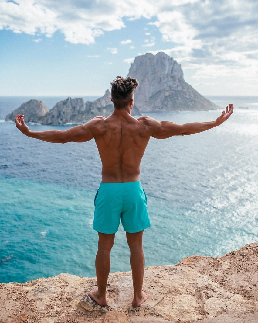 Antonio Pozo standing on a cliff overlooking a vast blue sea with his arms raised in the air