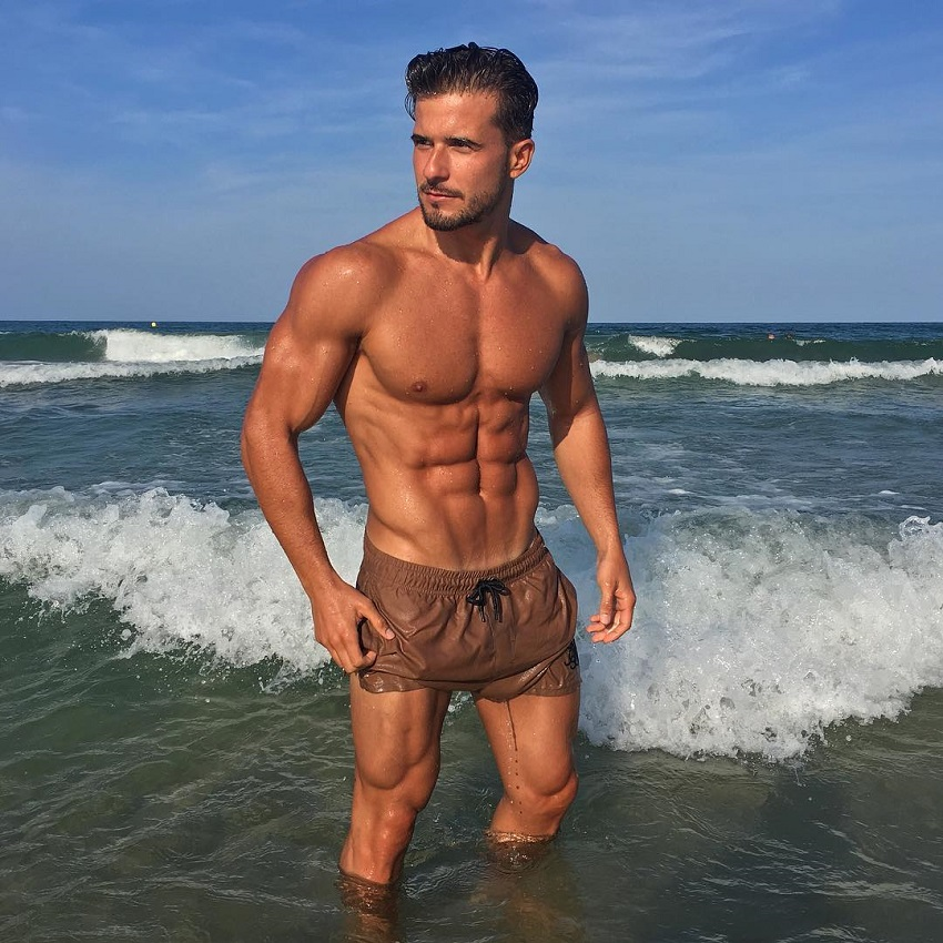 Antonio Pozo standing on the sea shore looking ripped and fit