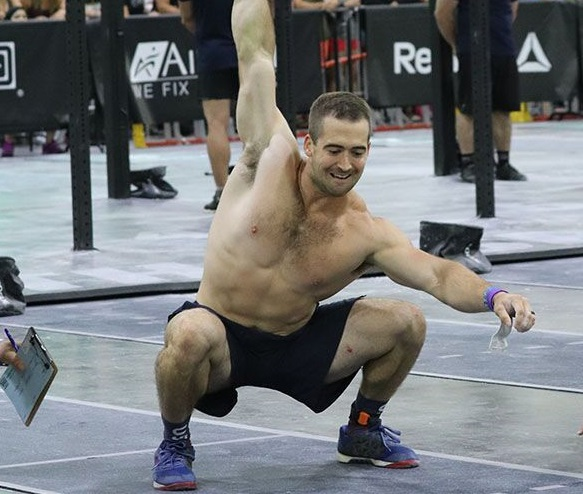 Ben Smith doing an overhead press with a dumbbell during a CrossFit event