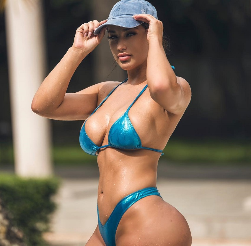 Breanna Soligny wearing a hat and green bikini looking curvy and fit