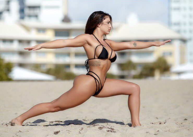 Breanna Soligny stretching on the beach in a black bikini looking curvy and fit