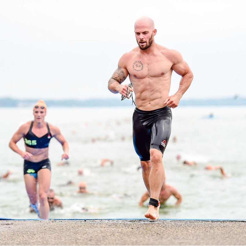Chris Spealler running on the beach competing against other CrossFitters